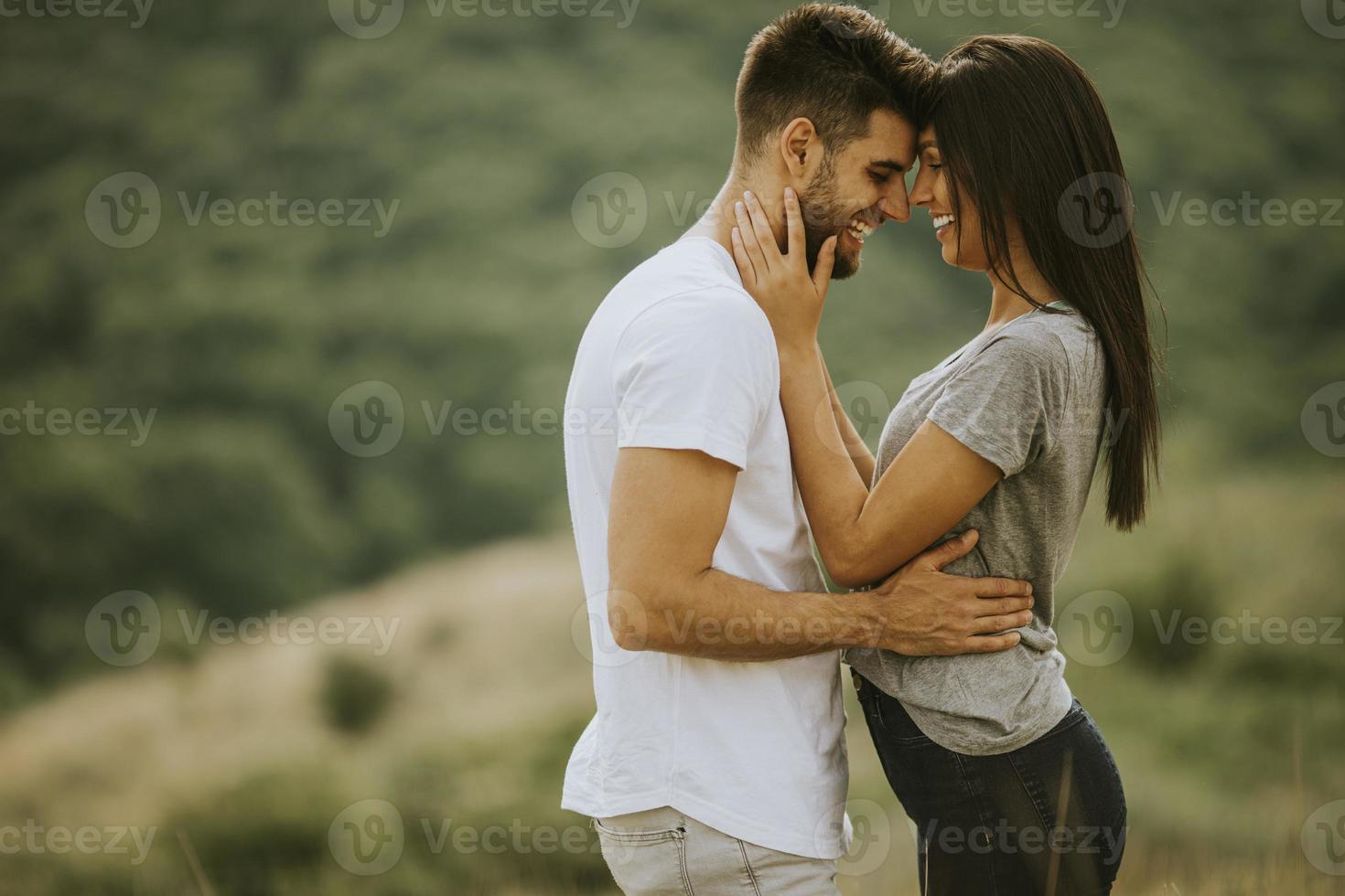 Happy young couple in love at the grass field photo