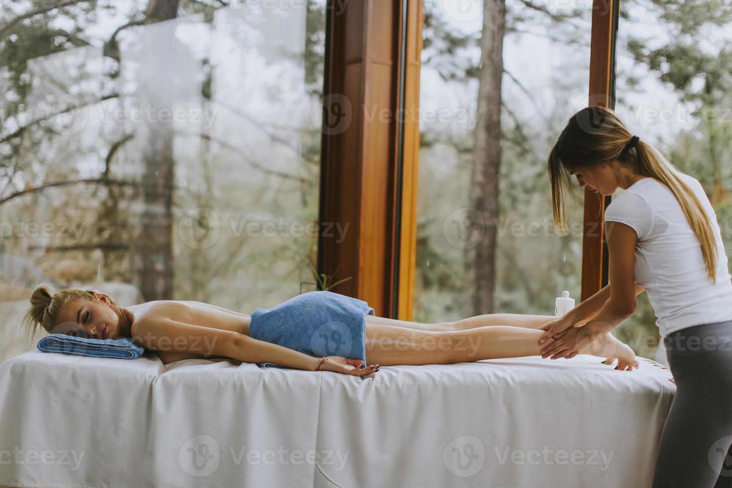Hermosa joven acostada y con masaje de piernas en el salón de spa durante la temporada de invierno foto