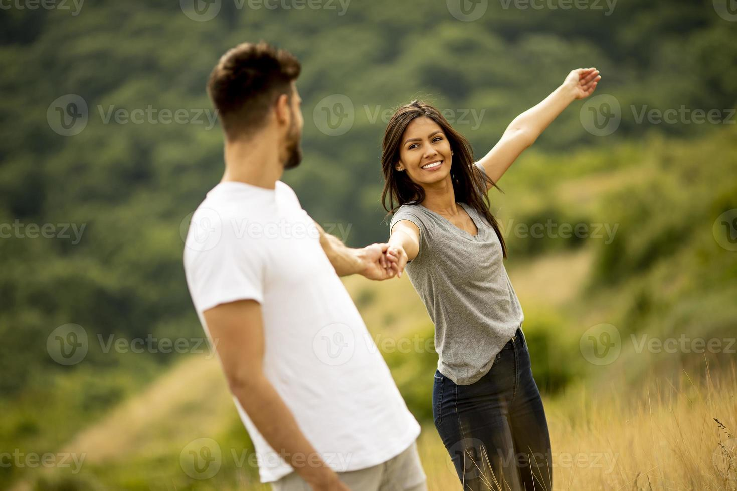 Happy young couple in love walking through grass field photo