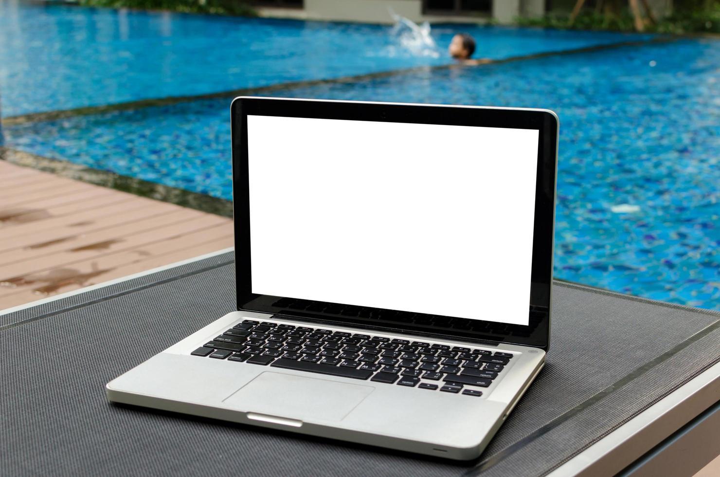 una computadora portátil en una tumbona junto a una piscina foto