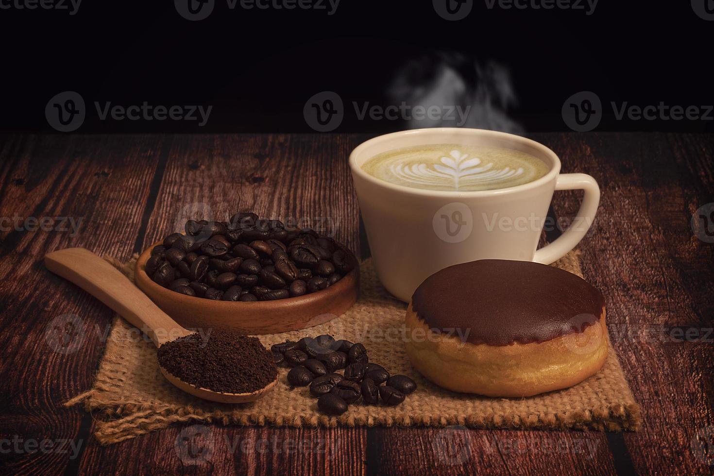 Donut, cup of steaming coffee with latte art, and coffee beans on burlap mat on a wooden table and black background photo