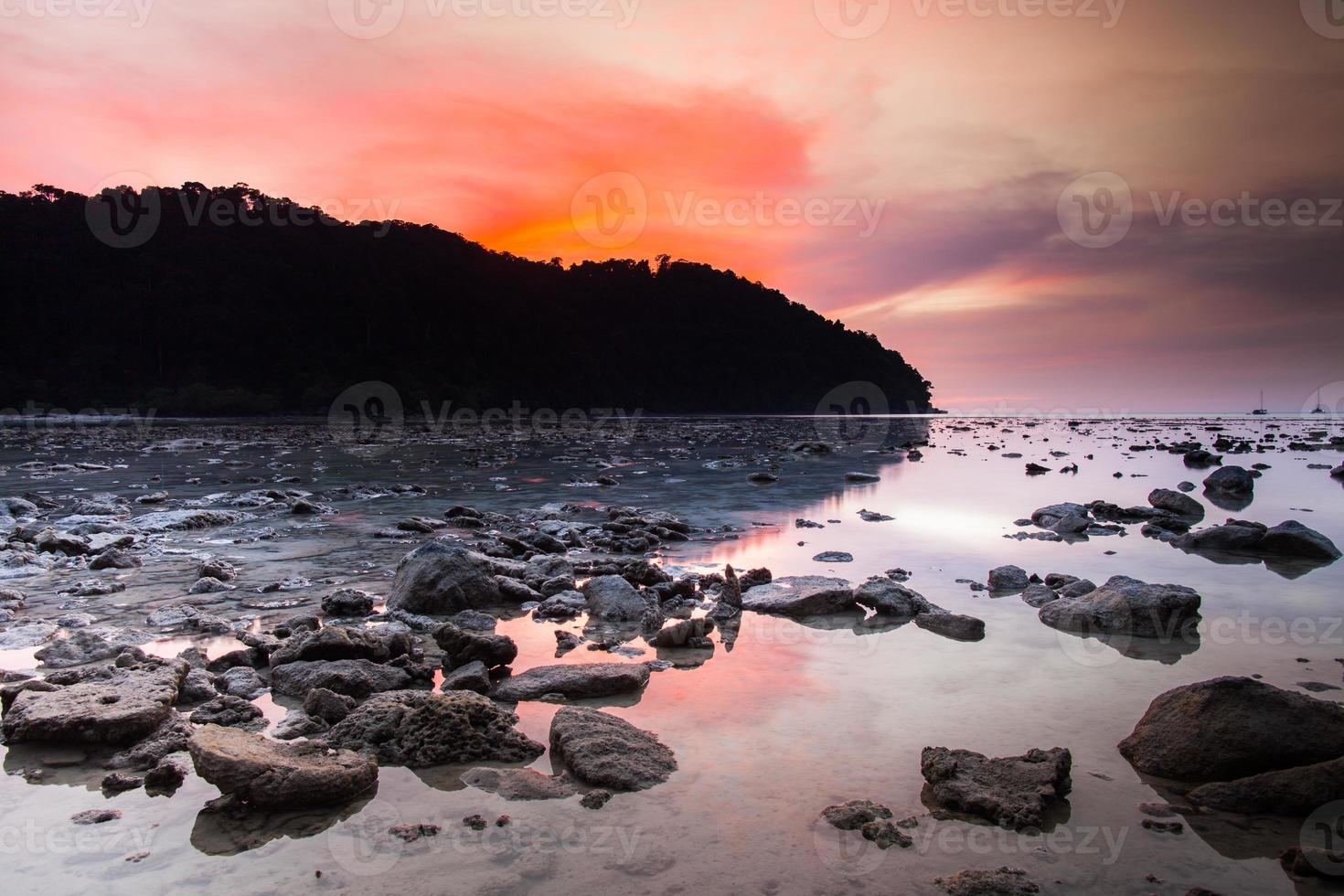 Colorful sunset over a rocky shore photo