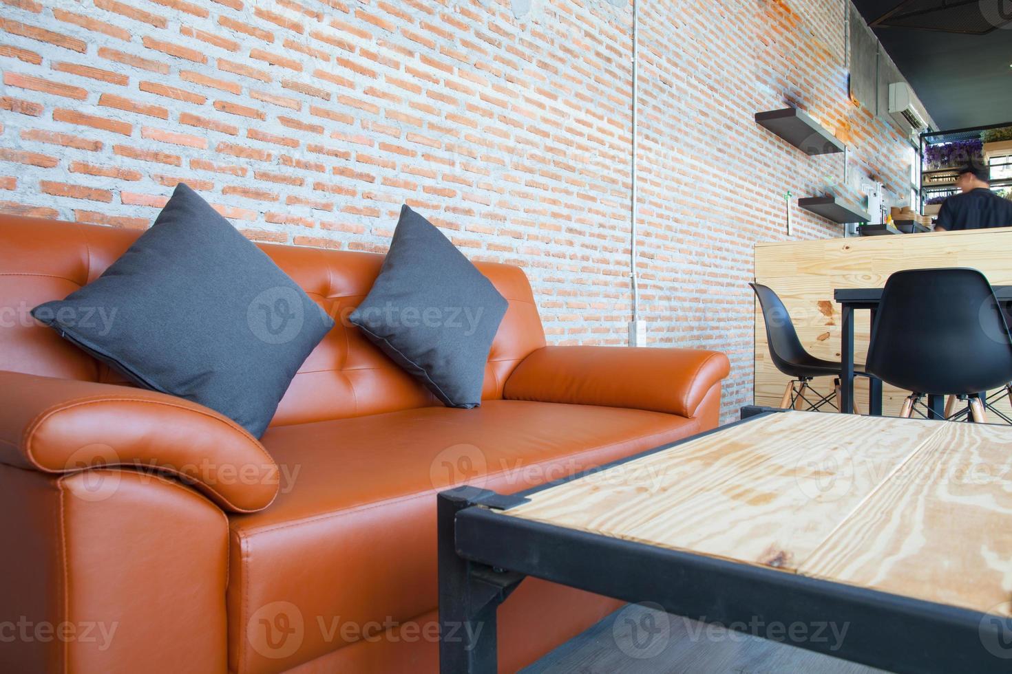 Sofá de cuero naranja con pared de ladrillo fondo marrón foto