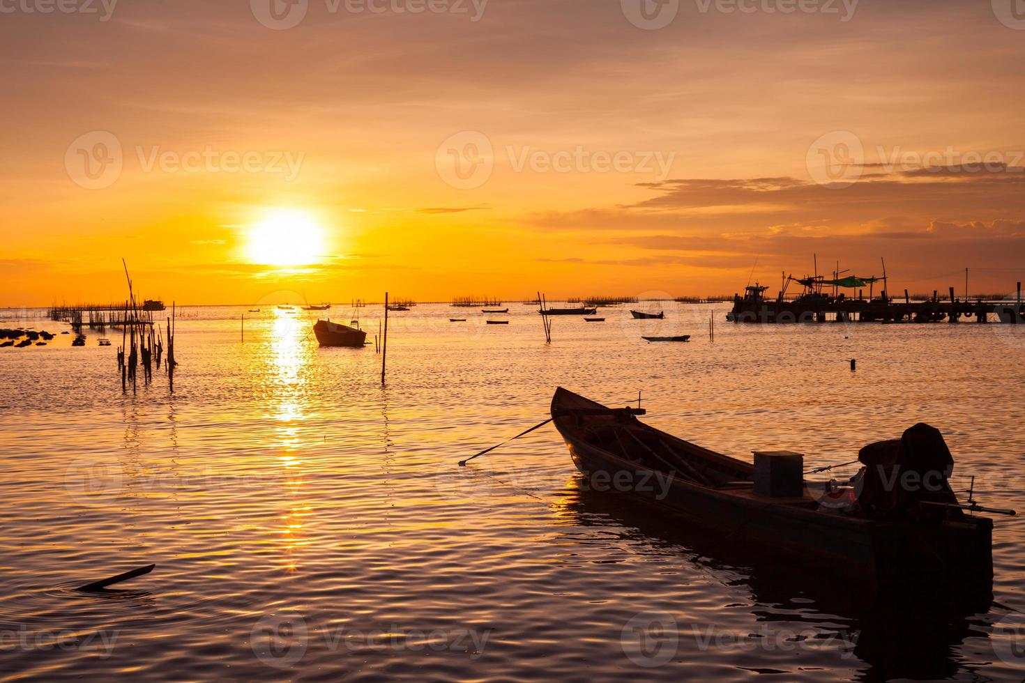 barcos en el agua con una puesta de sol naranja foto