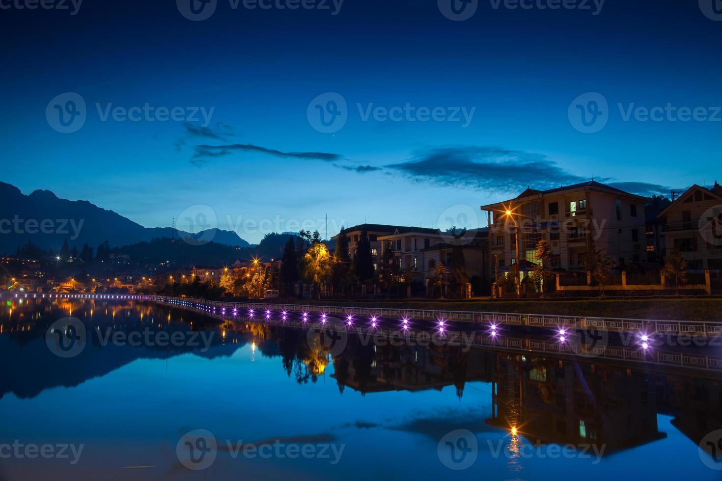 luces a lo largo del agua por la noche foto