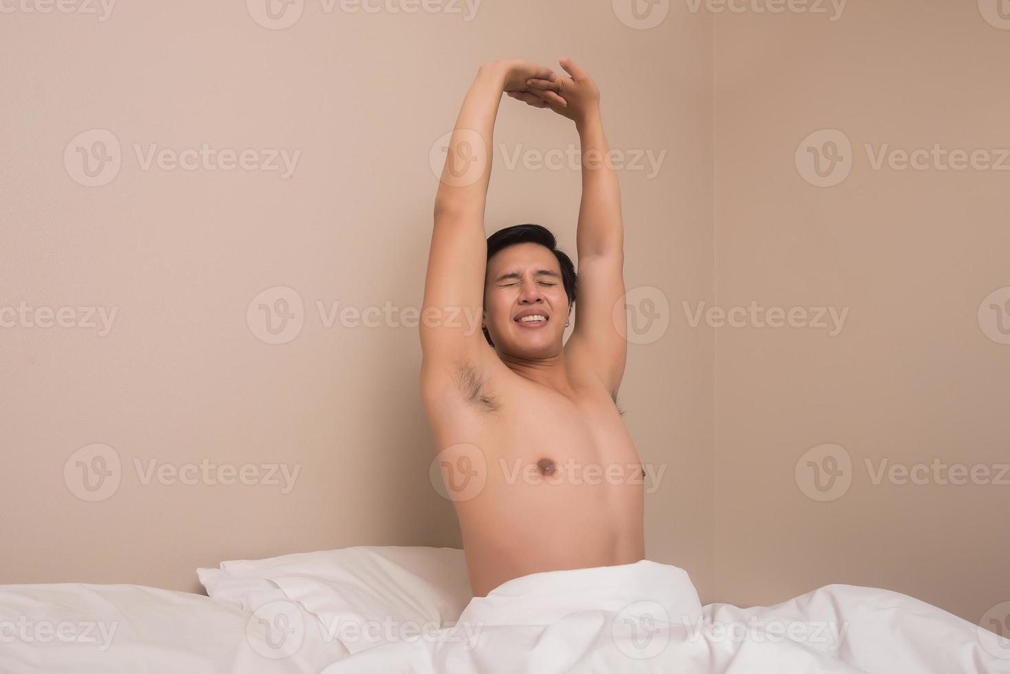 Guapo sonriendo mientras se estira en su cama en casa foto