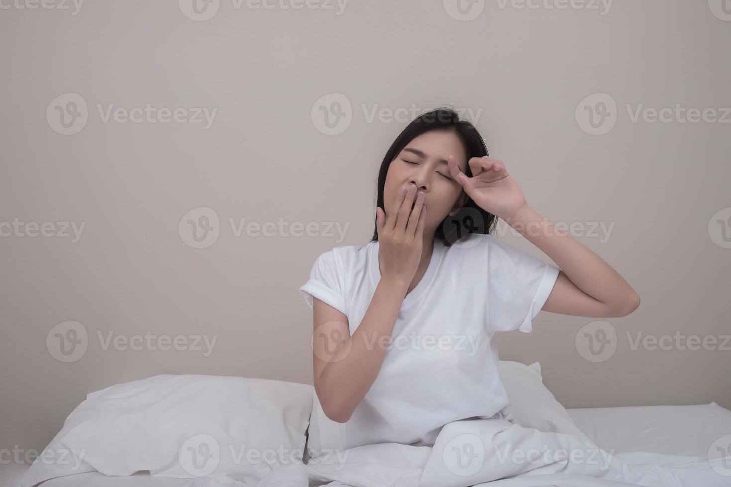 Mujer feliz que se extiende en la cama en casa por la mañana foto
