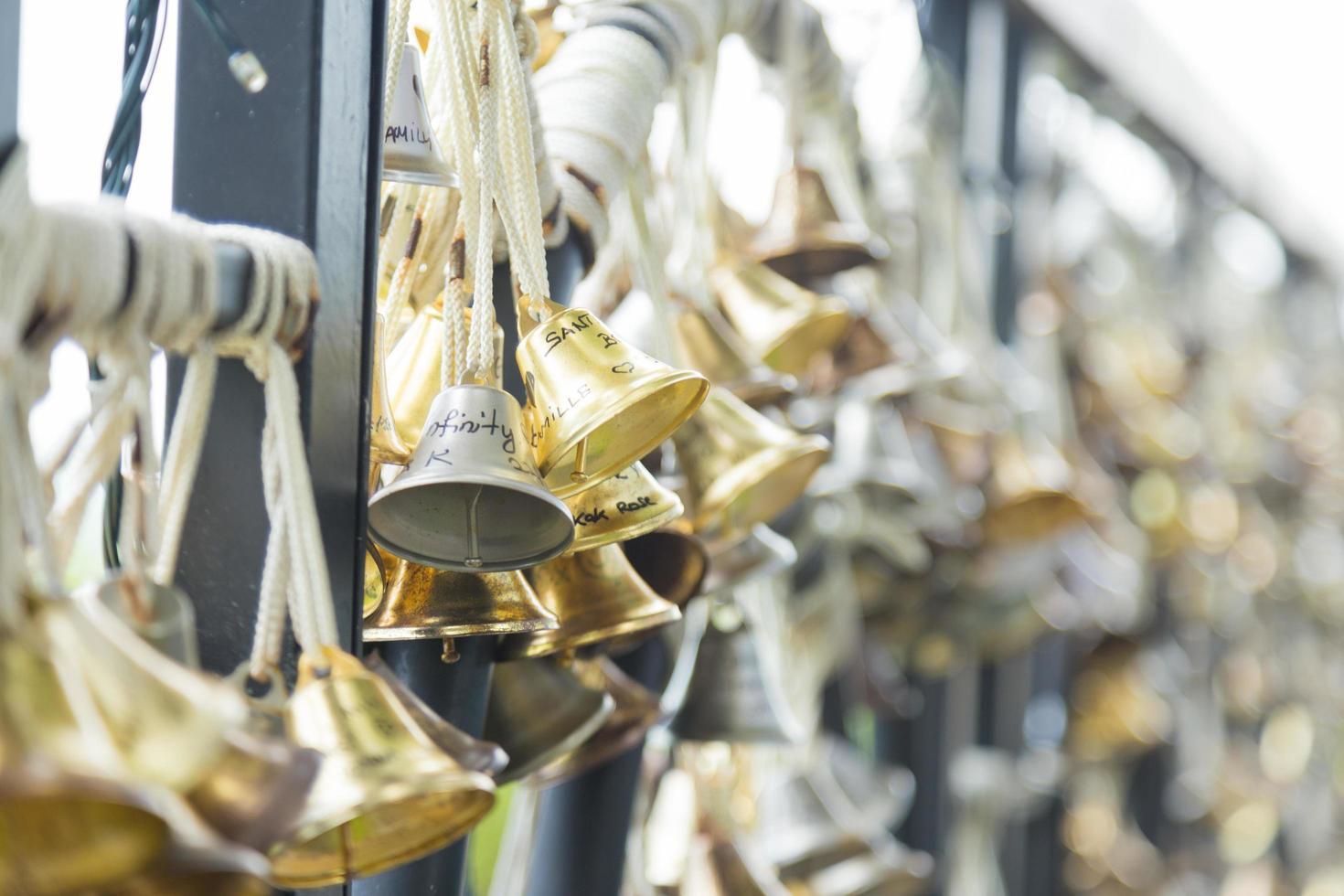 pequeñas campanas atadas a una cerca foto