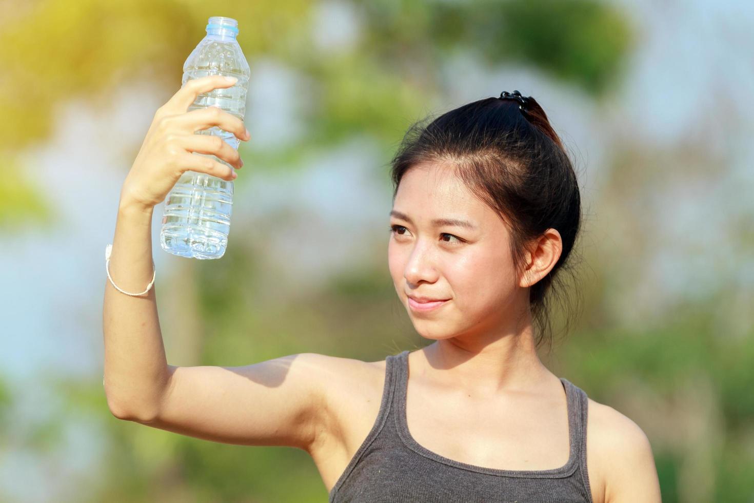 mujer deportiva bebiendo agua en un día soleado foto