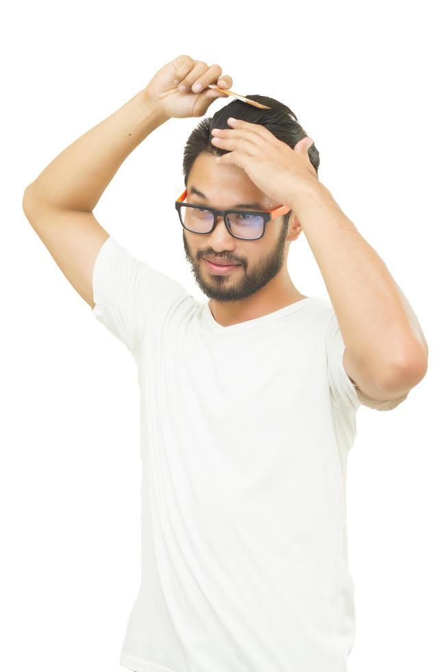 Hombre de blanco con cuello en v cepillarse el cabello sobre fondo blanco. foto