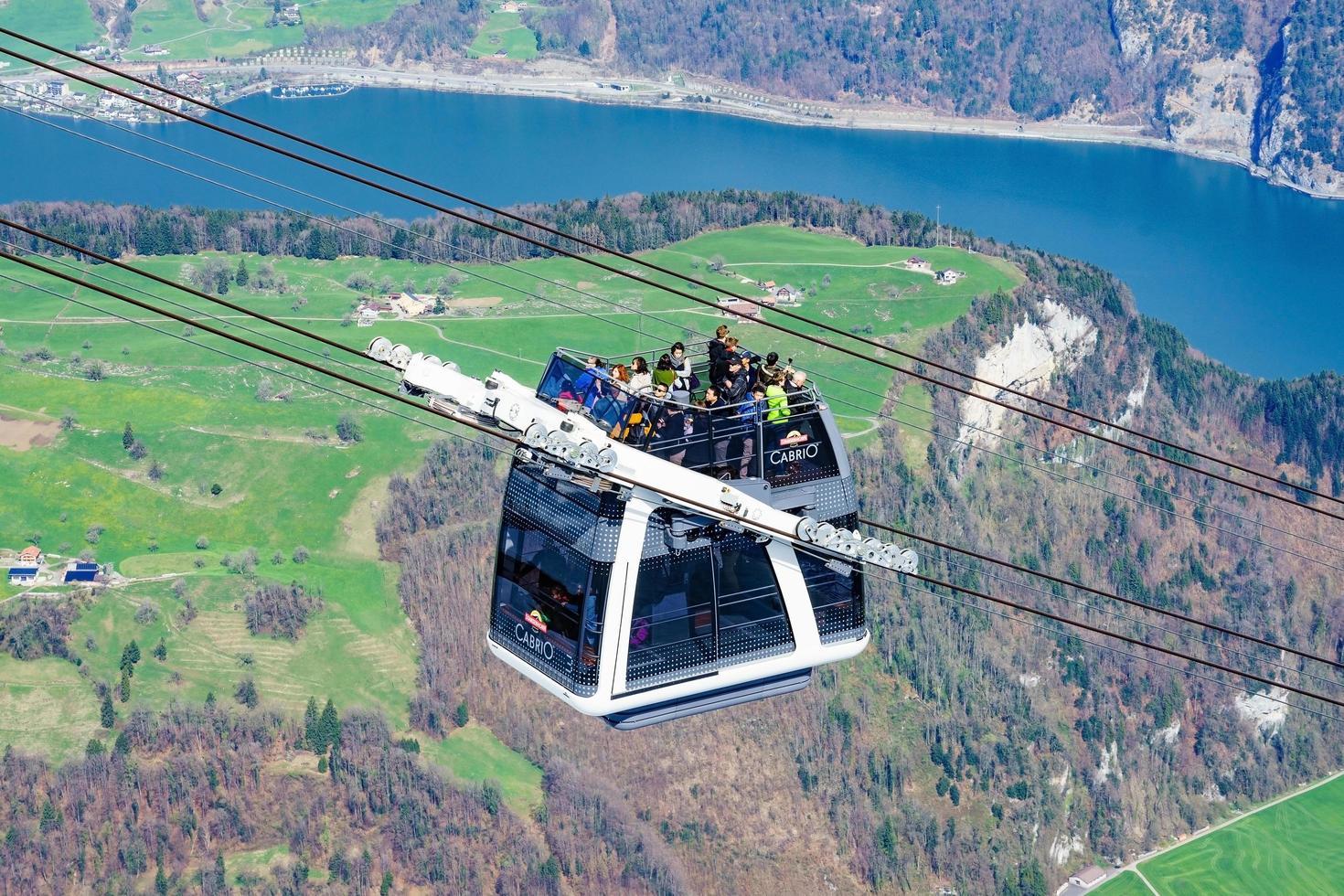 La gente en una góndola del teleférico cabrio Stanserhorn, Suiza foto
