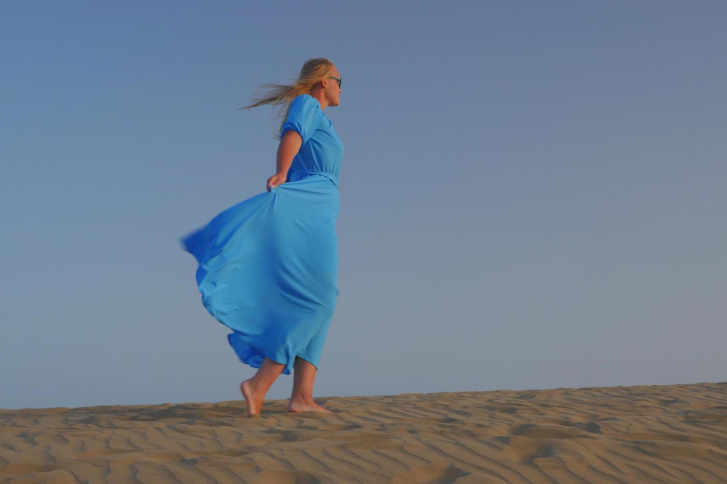 Mujer descalza caminando en la arena con un vestido azul foto