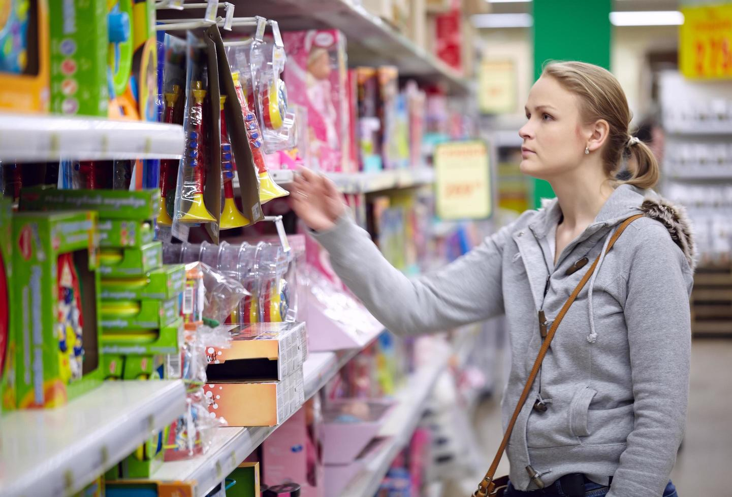 Woman choosing a toy for her kid photo