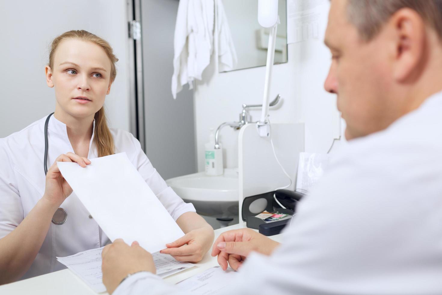 enfermera le muestra a un médico una hoja de papel en blanco foto