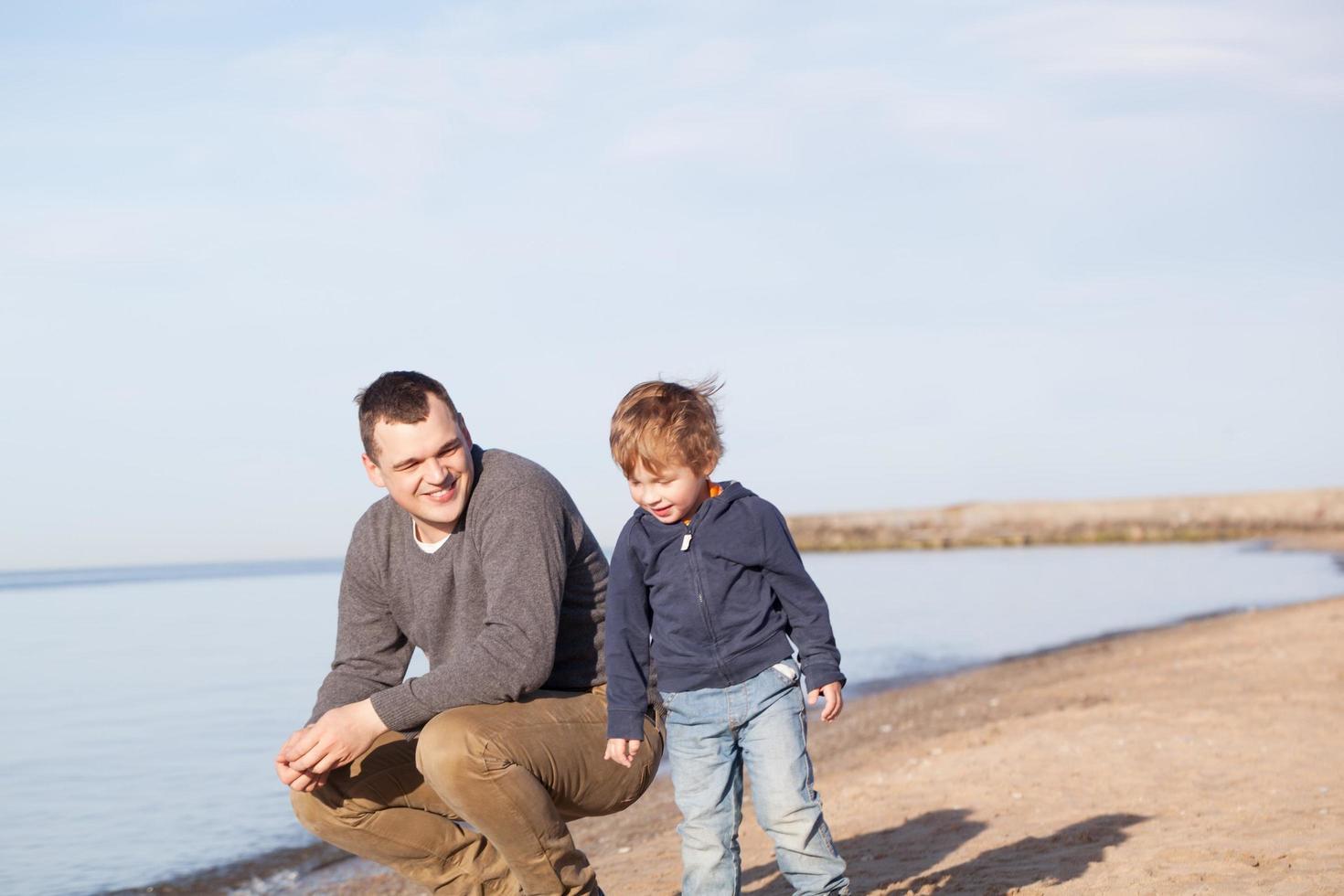 padre con su hijo pequeño en la playa foto