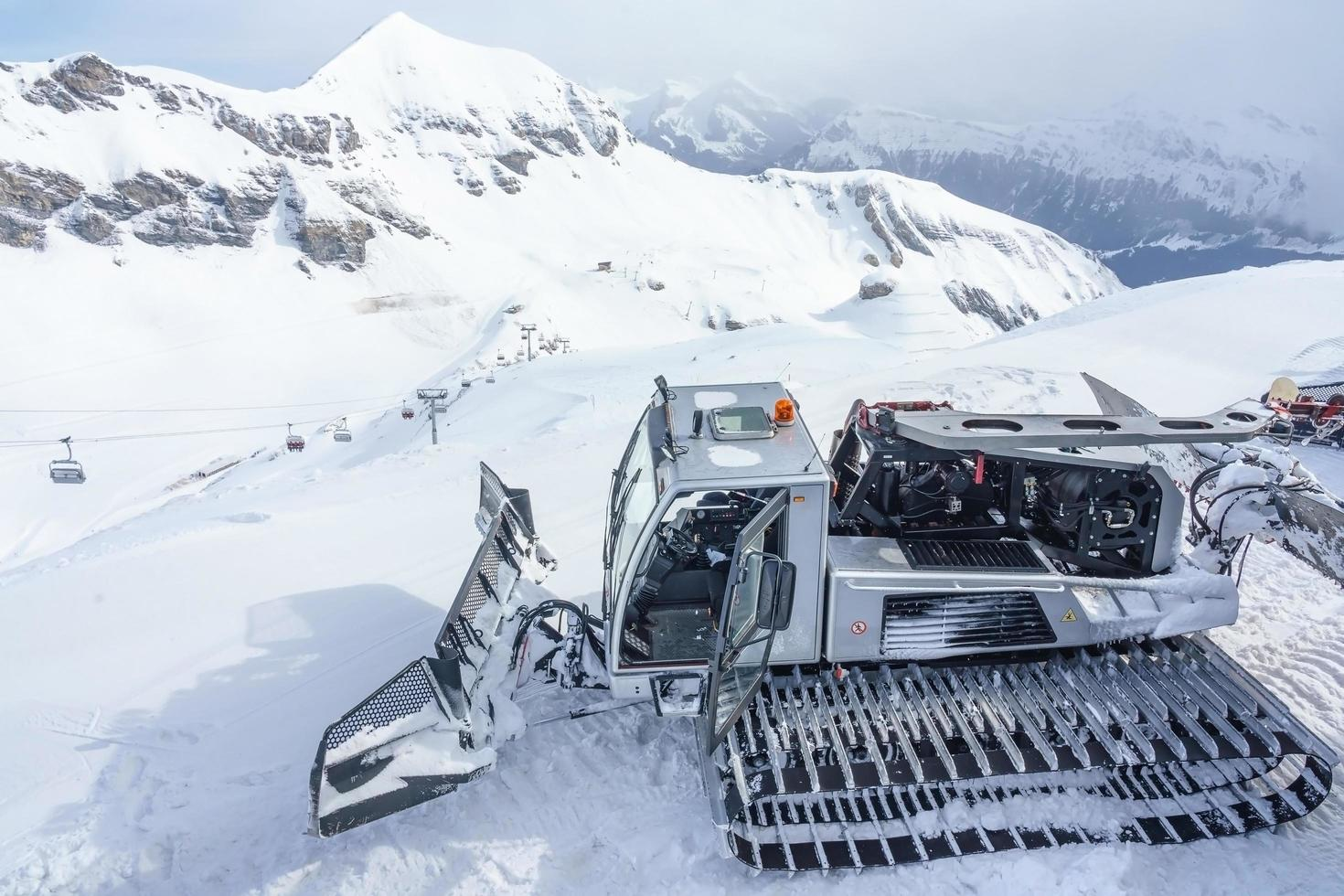 Snow-grooming machine on snow hill in the Swiss Alps photo