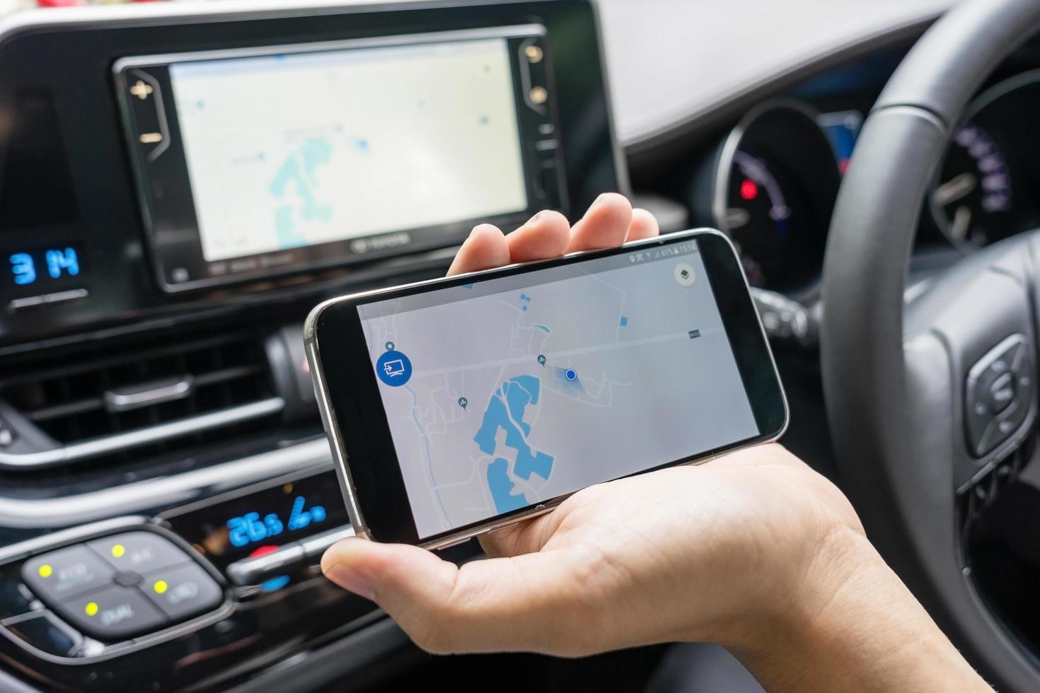 hombre en el coche con teléfono móvil negro con mapa foto