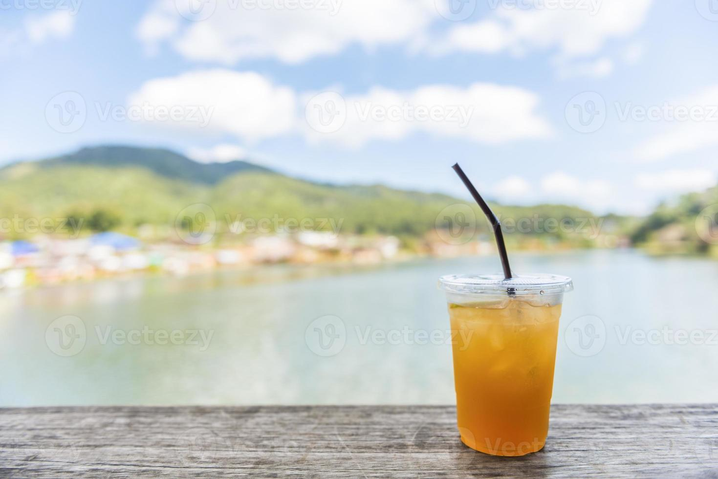 Té helado de limón sobre mesa de madera con vista al lago foto