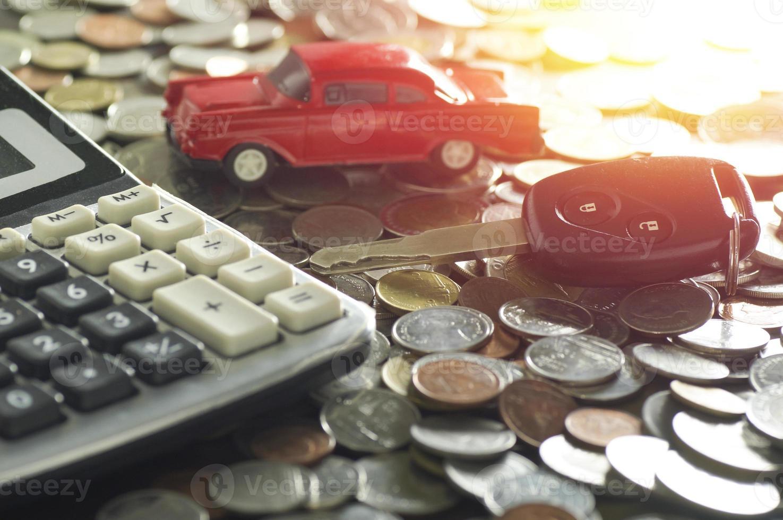 Llave del coche y modelo de coche rojo con monedas. foto