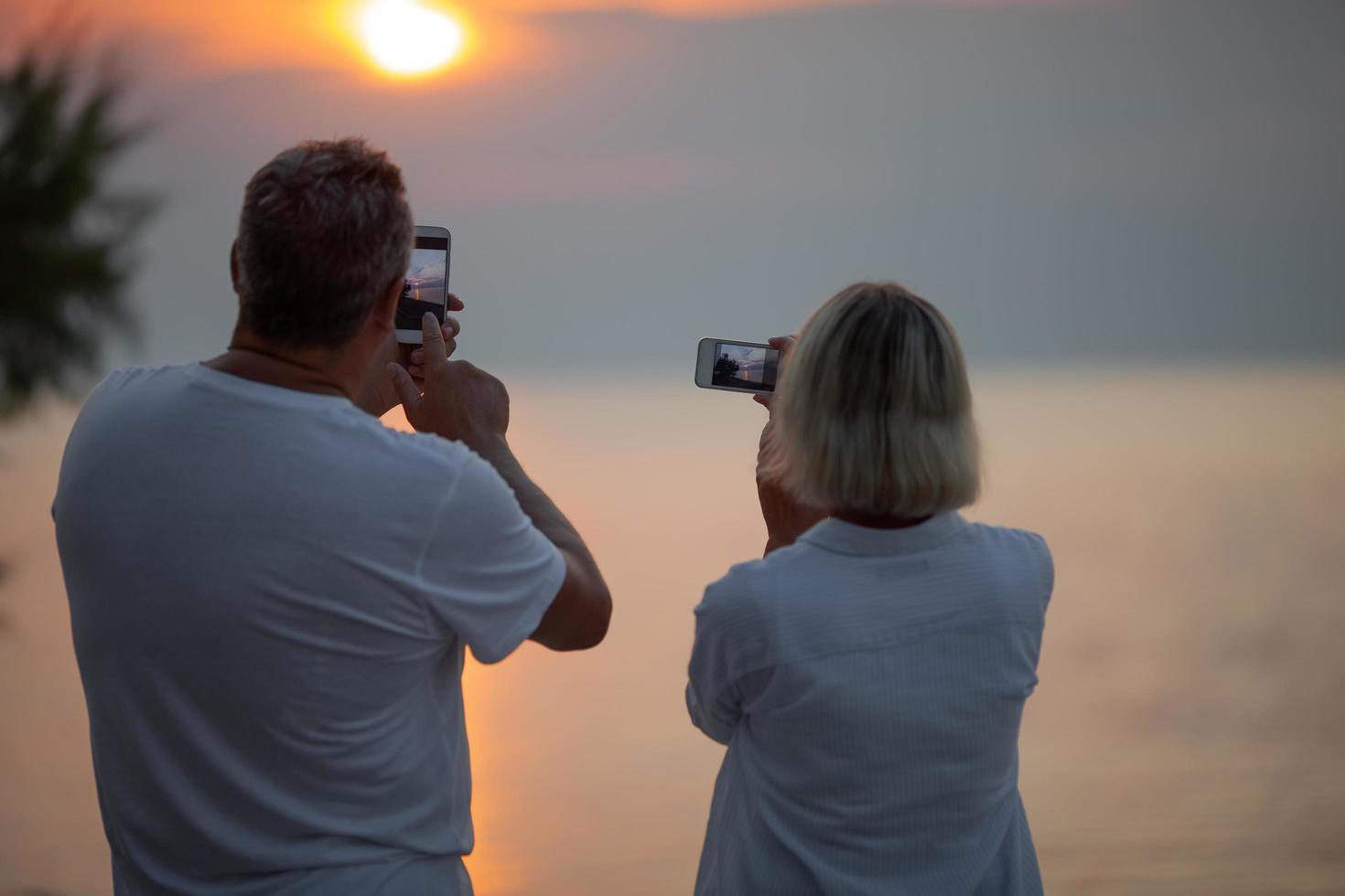 pareja tomando fotos de una puesta de sol