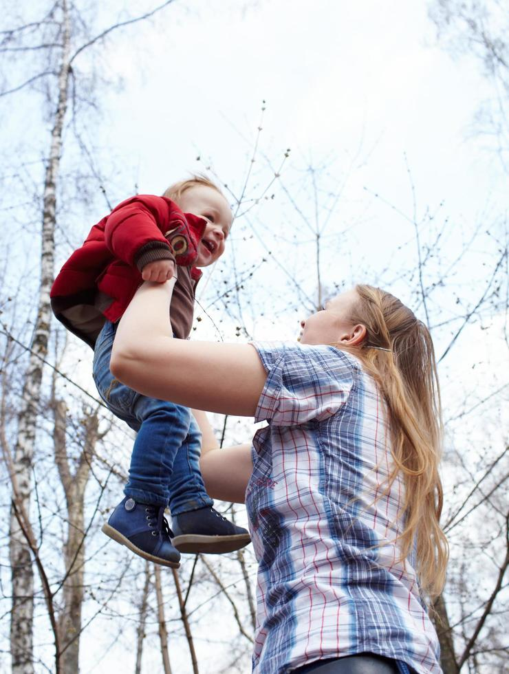 Mother holding son outside photo