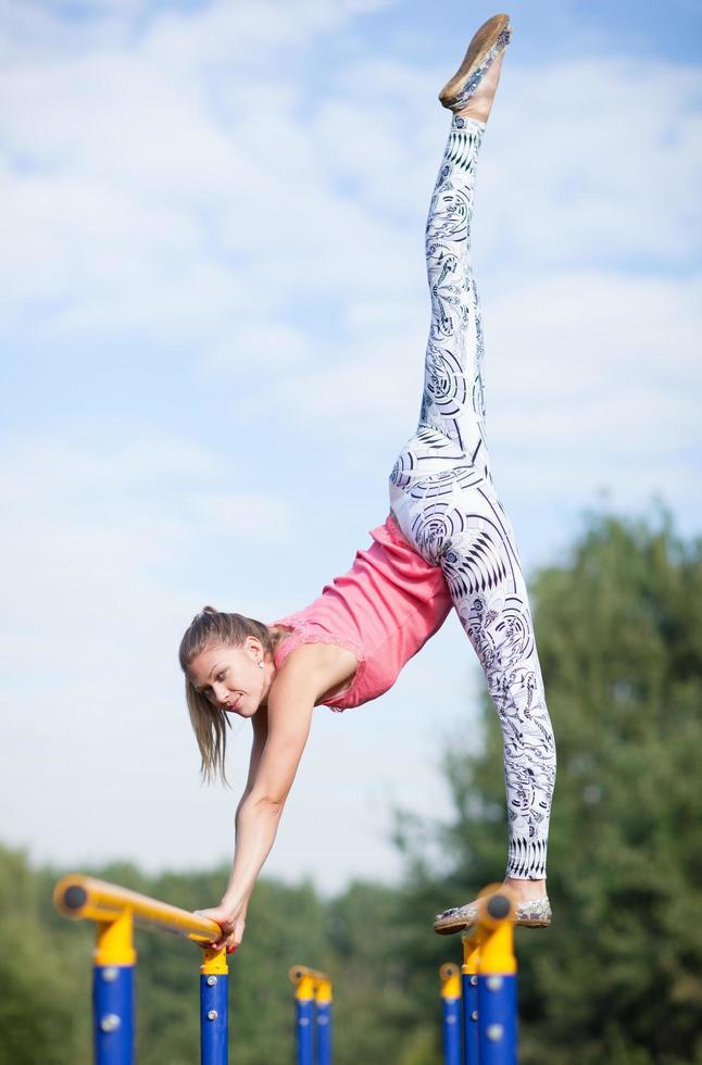 joven gimnasta en equilibrio sobre barras transversales foto