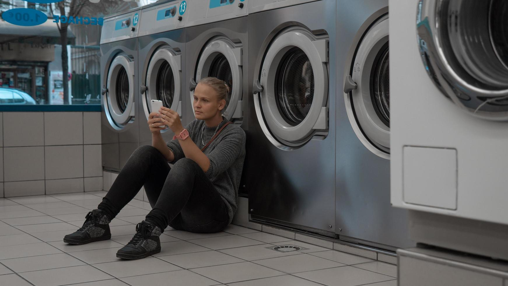Woman on her phone at a laundromat photo