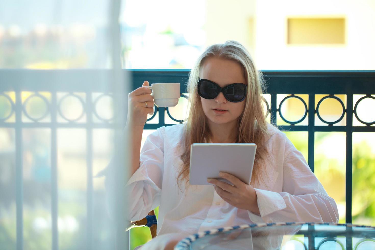 mujer usando una tableta y sosteniendo un café foto