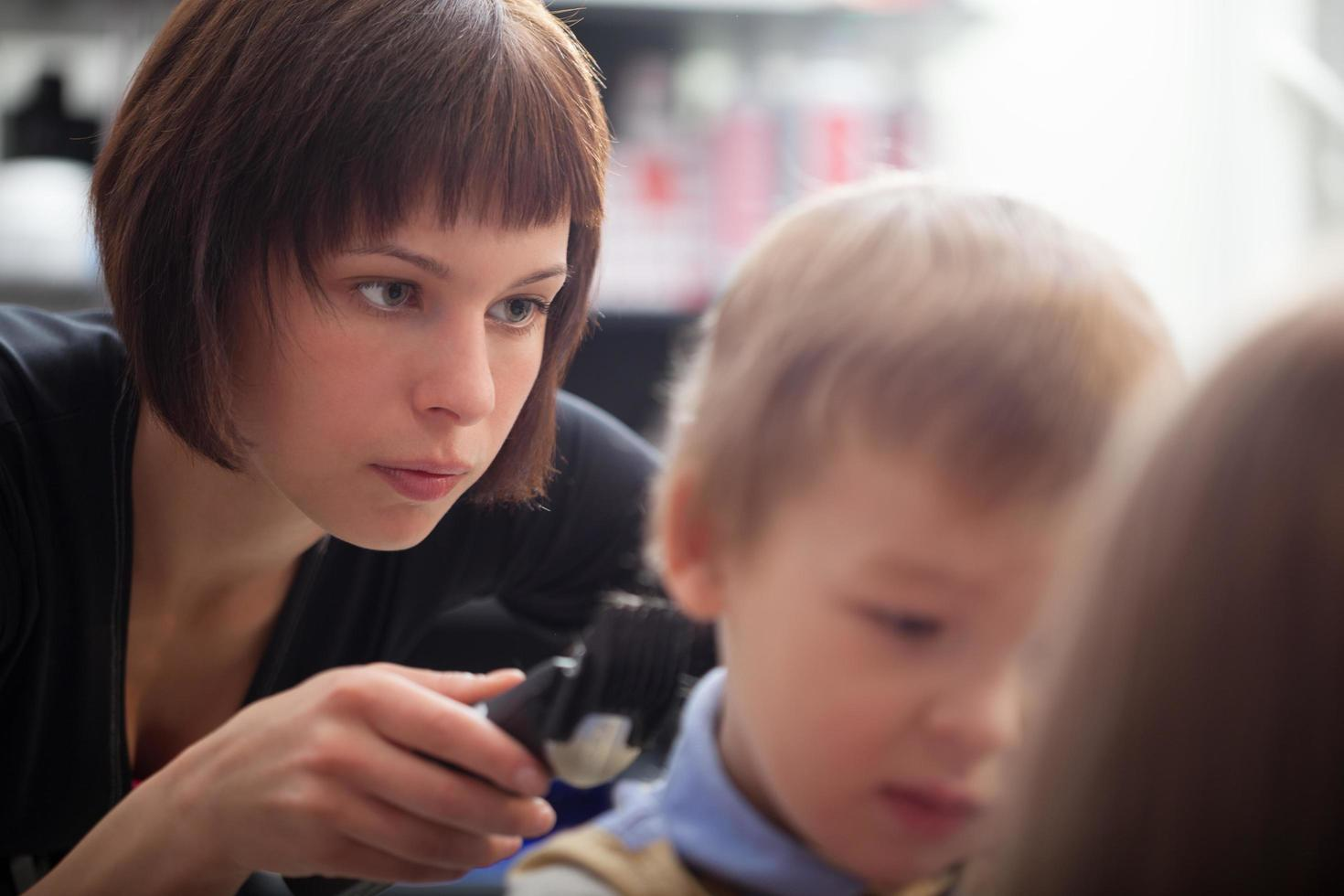 Hairstylist cutting a young boy's hair photo