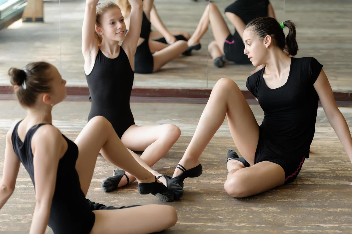 Three ballet dancers stretching in a studio photo