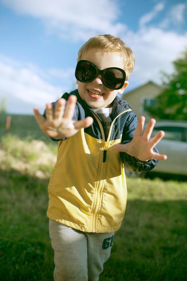 niño feliz en grandes gafas de sol afuera foto
