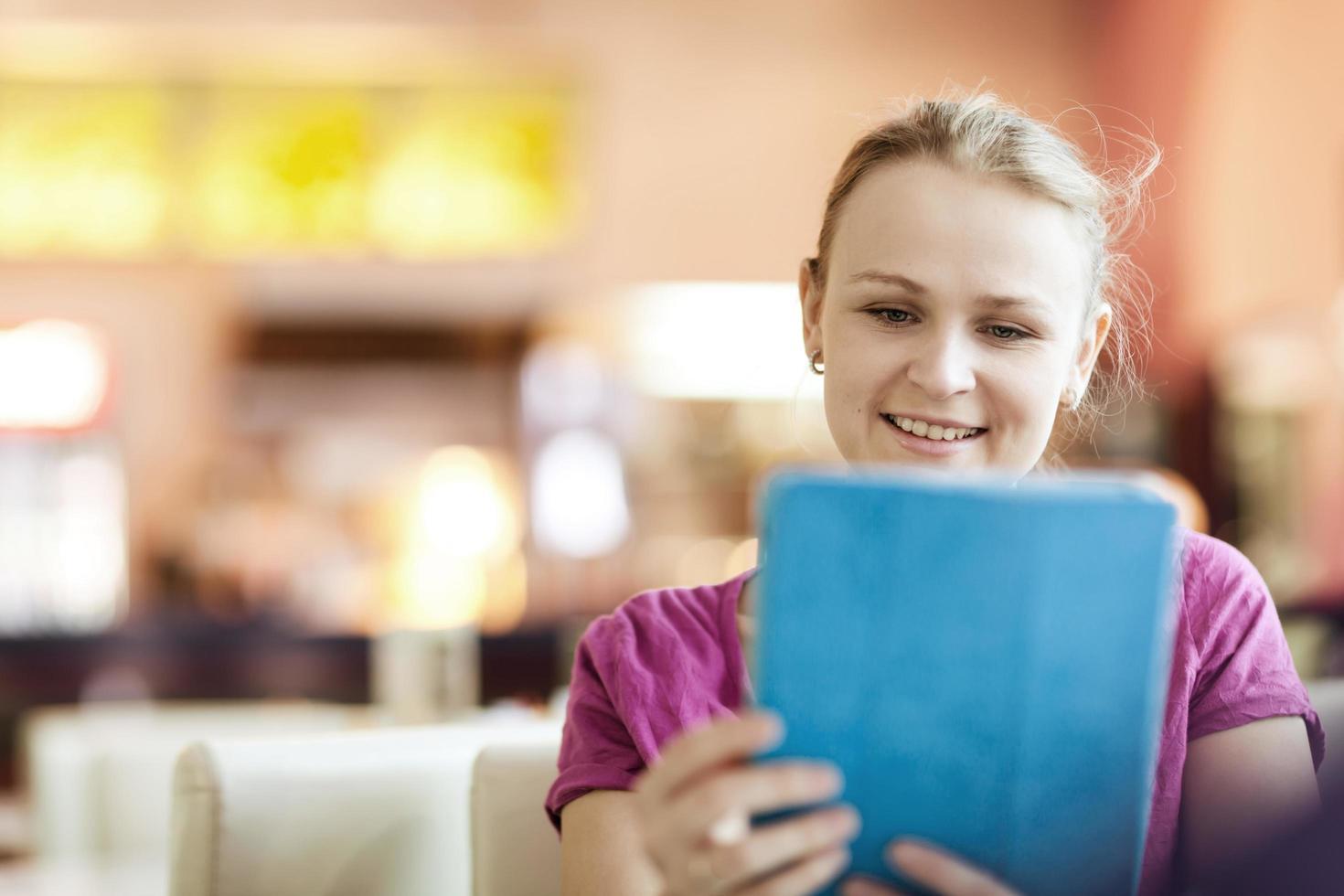 mujer feliz en un café usando una tableta foto