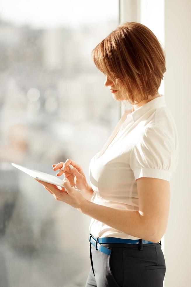Woman using a tablet near a window photo