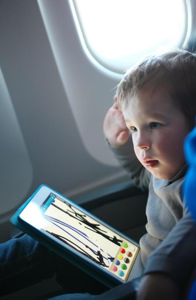 niño pintando en una tableta en un avión foto