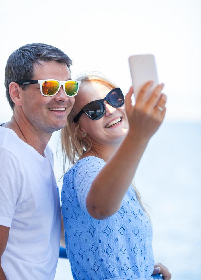 Cheerful couple in sunglasses taking a selfie photo