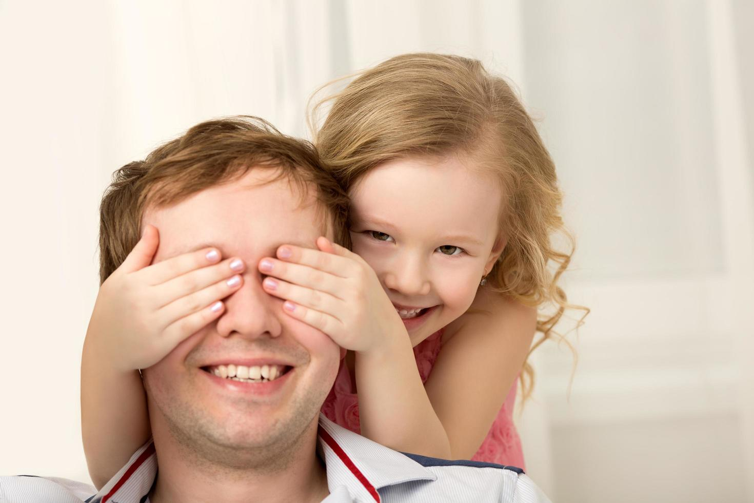 Daughter playing peekaboo with father photo
