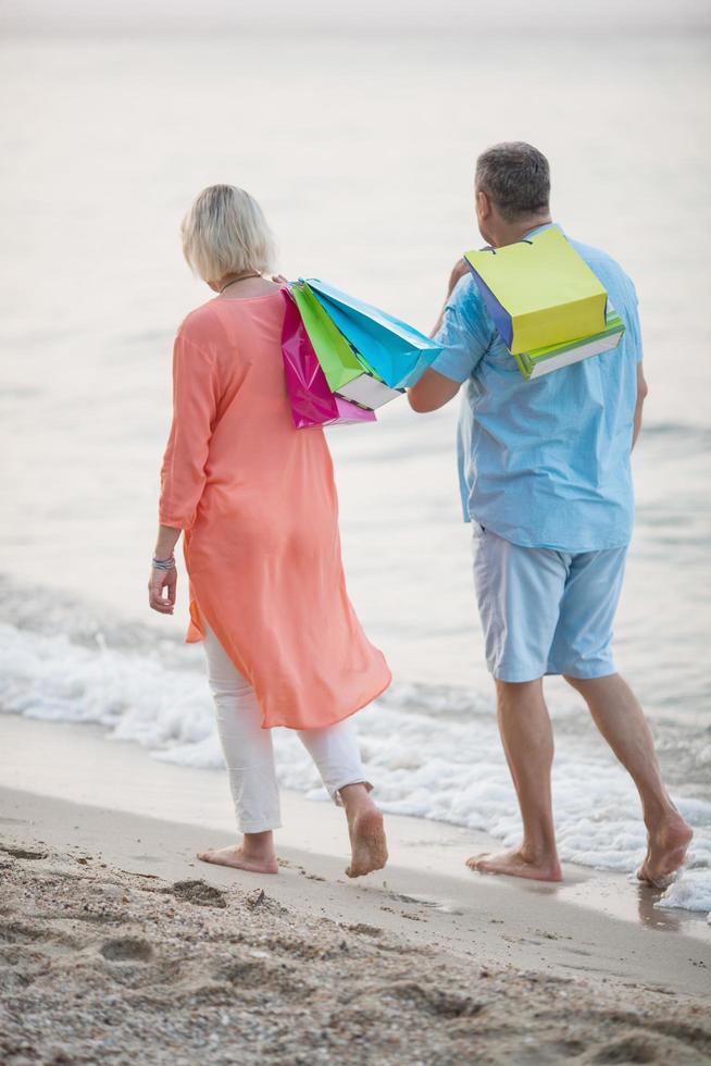 pareja caminando por la playa después de ir de compras foto