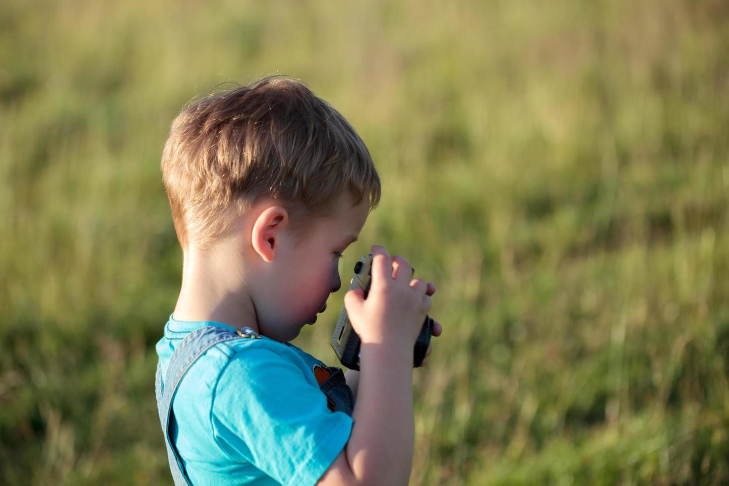 Little boy with camera outdoors photo