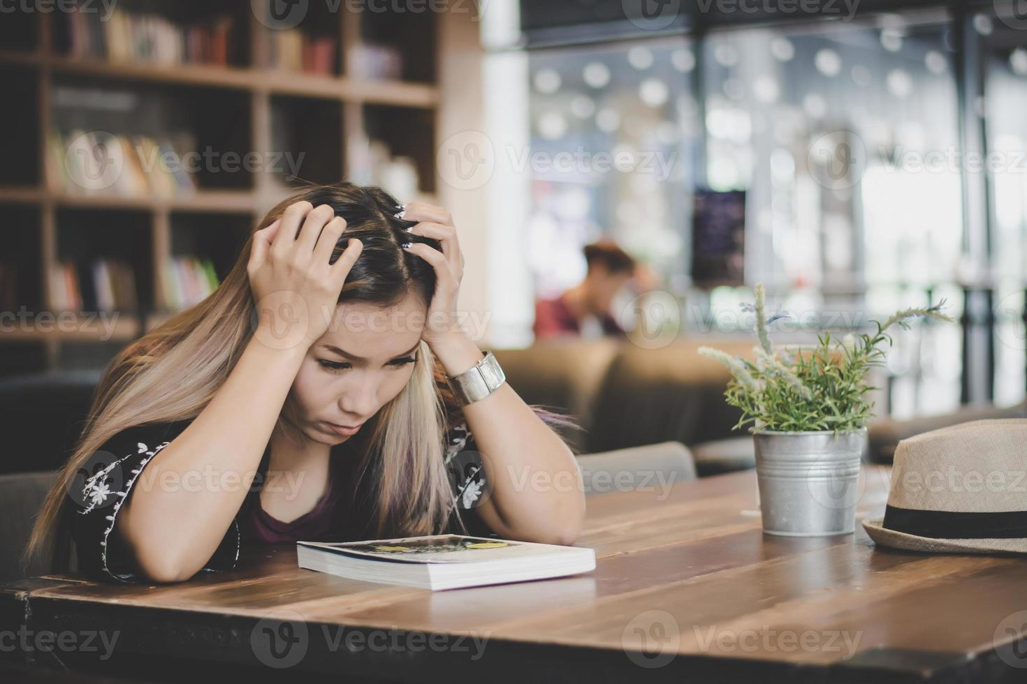 Business woman feeling stressed while sitting at cafe photo