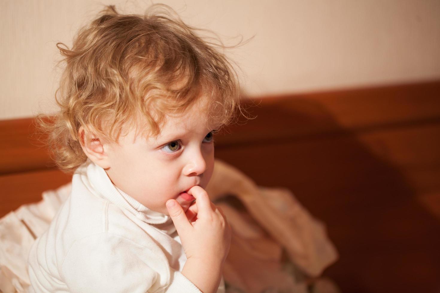 niño mirando hacia adelante con expresión pensativa foto