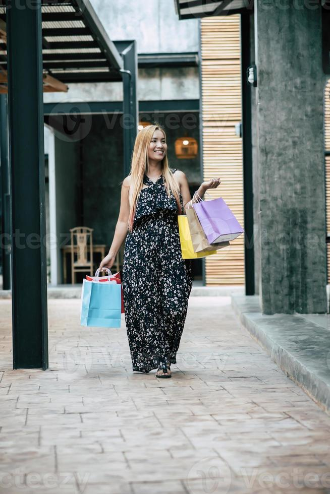 Portrait of a young happy woman with shopping bags walking in the street photo