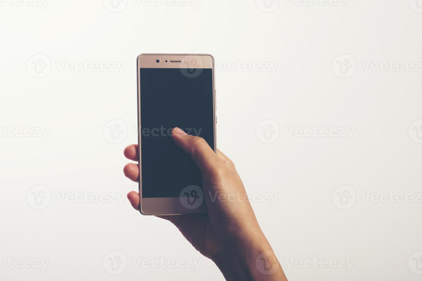 Close Up of a woman holding on mobile phone isolated on white background photo