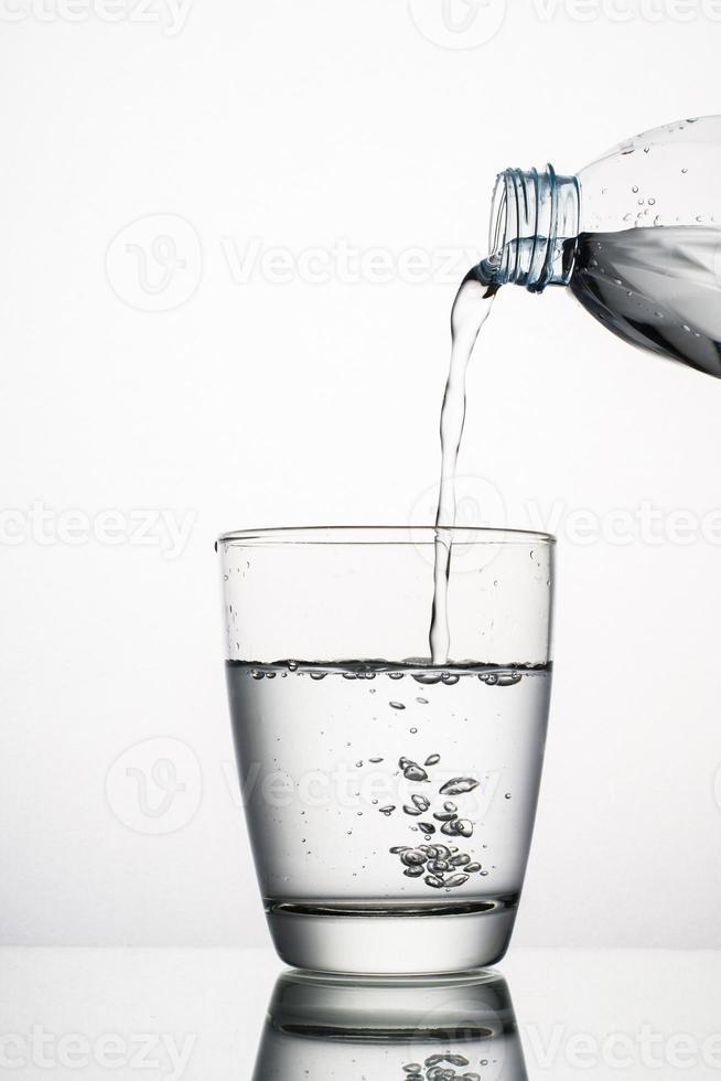 Close-up de verter agua en un vaso aislado sobre fondo blanco. foto