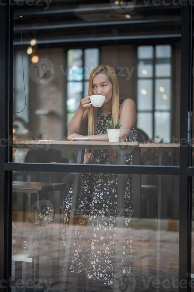 Beautiful woman in a cafe drinking coffee photo