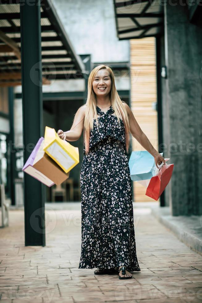 retrato, de, un, joven, mujer feliz, con, bolsas de compras, ambulante, en la calle foto
