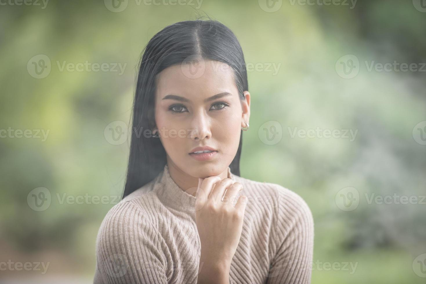 Portrait of Beauty young woman sitting in the park photo