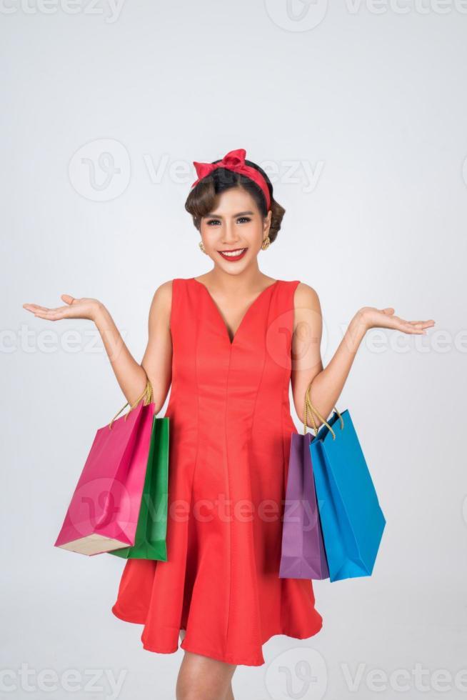 Beautiful Asian woman holding colored shopping bags photo