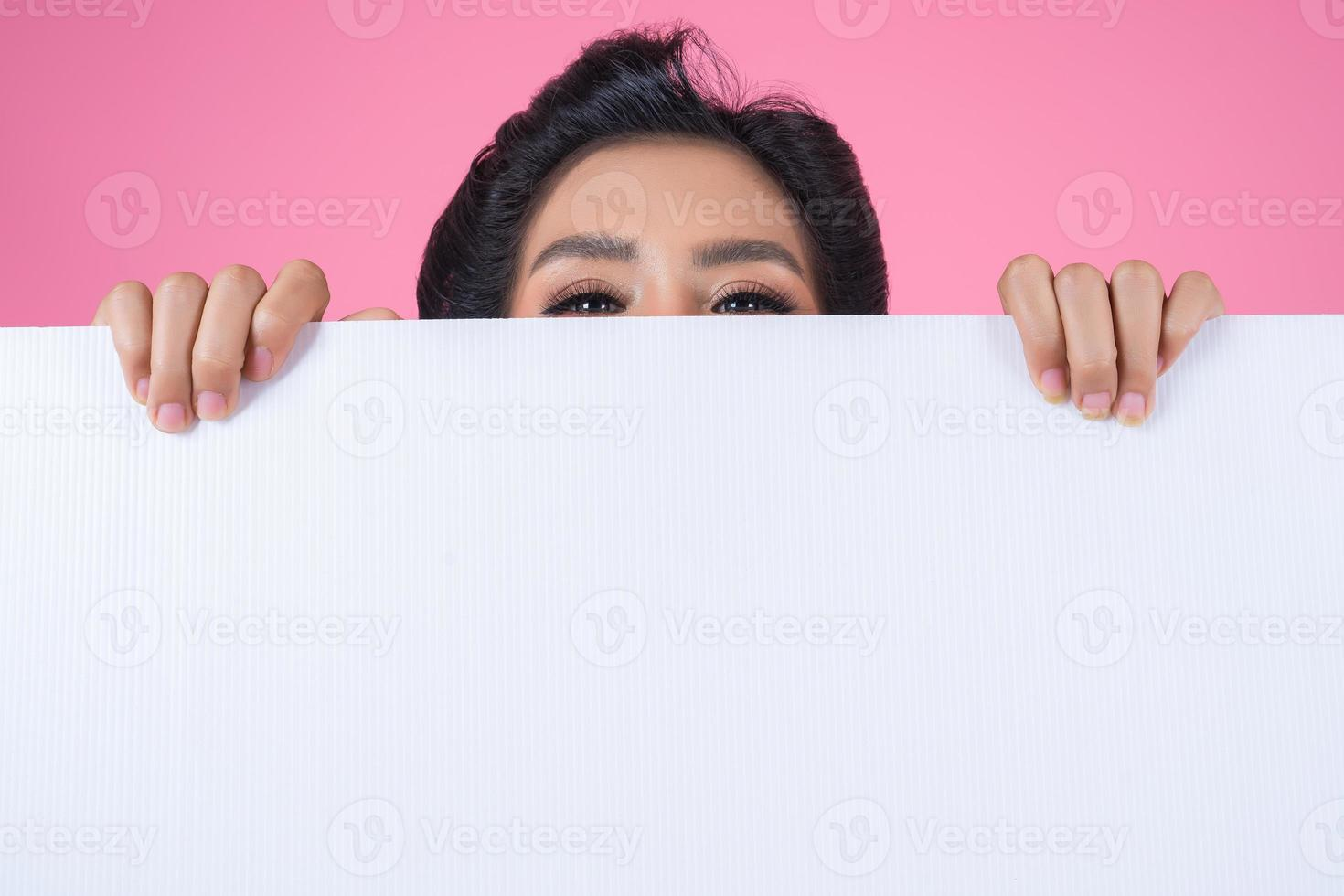 Portrait of a fashionable woman displaying a white banner photo