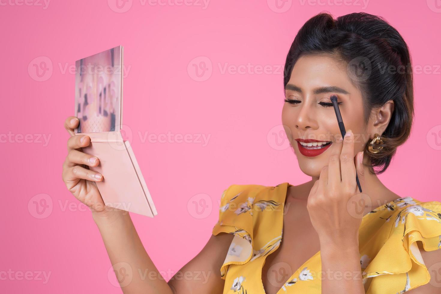 Portrait of a woman with makeup and cosmetic brush photo