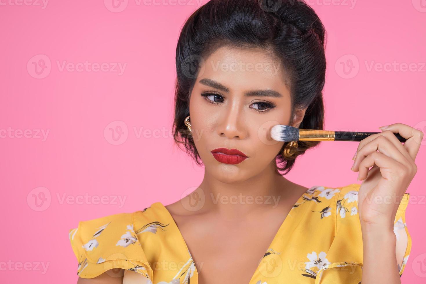 retrato de una mujer con pinceles de maquillaje foto